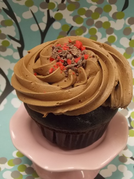Chocolate cherry cupcake with milk chocolate buttercream and a sprinkling of chocolate cherry bark