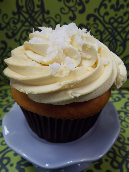Pineapple coconut cupcake with pineapple buttercream and a sprinkle of coconut on top