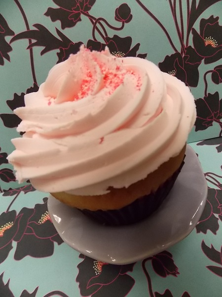 Vanilla cupcake filled with cream cheese and topped with Washington Cherry buttercream and a sprinkling of cherry bark